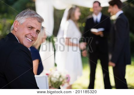 Portrait of man smiling in park during wedding
