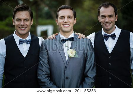 Portrait of smiling bridegroom and best man standing in garden
