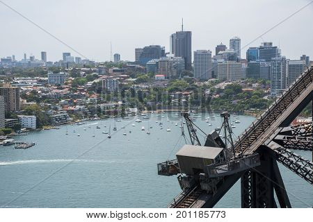 SYDNEY,NSW,AUSTRALIA-NOVEMBER 20,2016: Detail of suspended scaffolding with hanging basket on the Sydney Harbour Bridge with view over boats in harbour and waterfront architecture in Sydney, Australia.