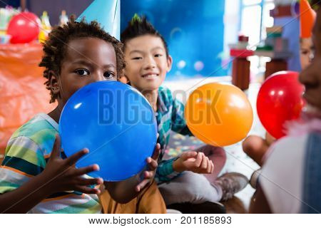 Portrait of children playing with colorful balloon in rood during party