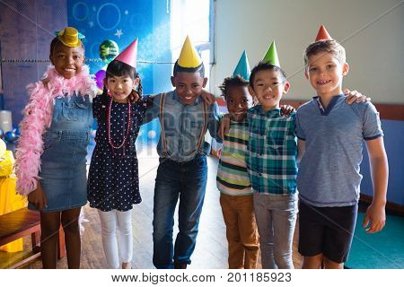 Portrait of happy friends with arm around standing against wall during birthday party