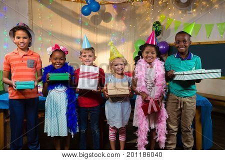 Portrait of children holding gifts while standing by table