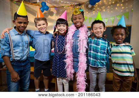 Portrait of smiling friends with arm around standing against wall during birthday party