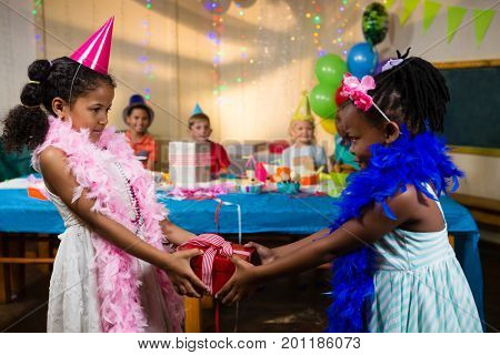 Side view of girl giving gift to friend during birthday party