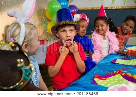 Boy making face while sitting with friends at table during birthday party