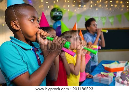 Children blowing party horns while standing by table during birthday party