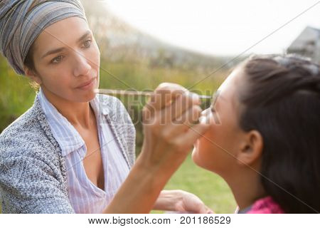 Ypung woman applying face paint on girl face during birthday party
