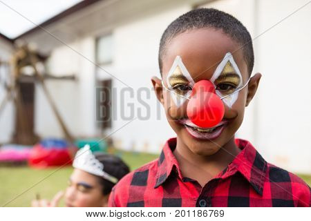 Portrait of boy with face paint wearing clown nose during birthday party in yard