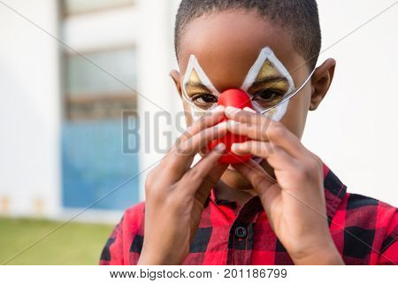 Close up portrait of boy wearing clown nose during birthday party in yard