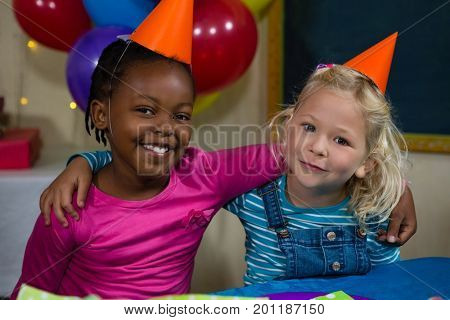Portrait of girls with arm around sitting at table during birthday party