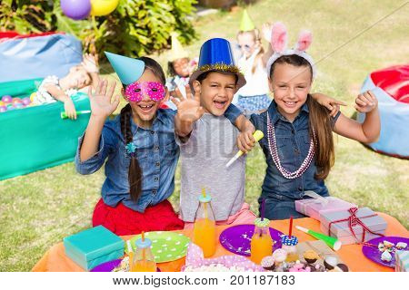Portrait of children gesturing while sitting at table in yard during party