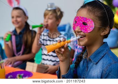 Close up of girl wearing eye mask blowing party horn with friends in background