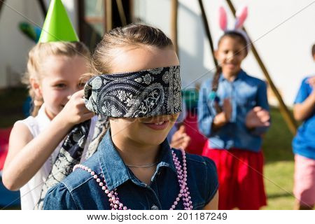 Girl blindfolding friend while playing in yard during birthday