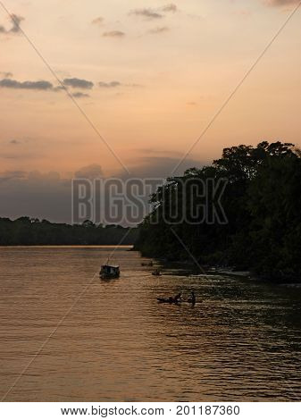 Sunset on the Amazon river. Some small canoes with children playing in the Amazon river at sunset. The picture was taken in the Paranà State Brazil