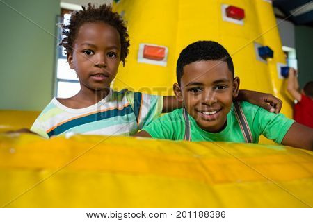 Portrait of happy friends with arm around sitting on bouncy castle