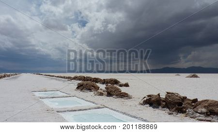 White salt harvesting pools in the middle of a huge salt flat. The rainy clouds already pass the Andes and are coming closer. The picture was taken in Salinas Grandes Argentina