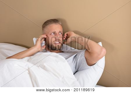 Troubled Young Man Lying On Bed Covering His Ears To Avoid Noise