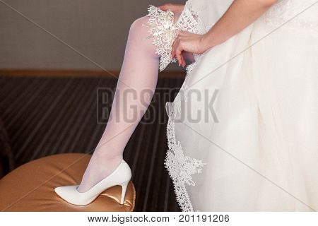 beginning of the wedding day. the bride wears a white wedding garter