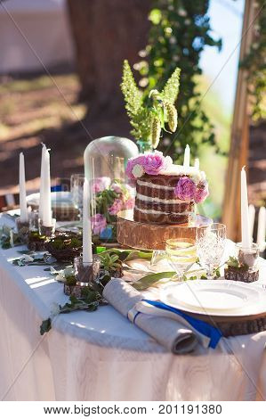 Puffy wedding cake with flowers on decor table with candles