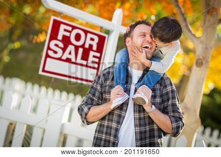 Young Mixed Race Chinese and Caucasian Father and Son In Front of For Sale Real Estate Sign and Fall Yard.