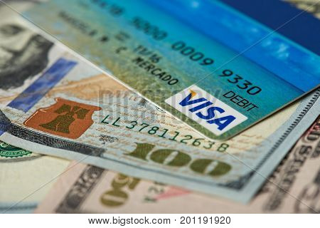 New york, USA - August 24, 2017: Visa debit card close-up on dollar bill background. Visa logo on debir card