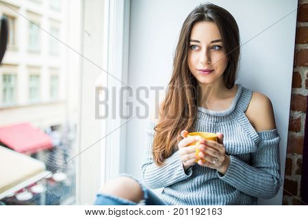 Young Girl Enjoying An Ideal Day Sitting In The Window-sill. Wearing Casual Denim Jeans And Blouse,