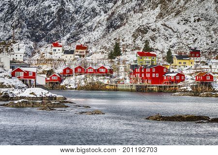 Red Wooden Traditional Huts Use Built With One End Of Pole in Water. Hamnoy and Reine Villages Houses of Lofoten Islands in Norway. Horizontal Image