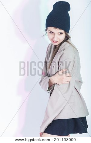 Youth Lifestyle Concepts. Portrait of Happy and Glad Exclaiming Thin Brunette Girl in Trendy Jacket Posing in Sexy Skirt On White. Vertical Image Orientation