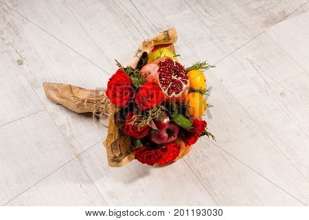 Beautiful bouquet of roses and fruits. Original present for gourmet, eatable composition of mandarin, apples, pomegranate and roses.