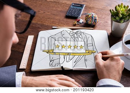 Man Drawing Five Star Hospitality Service Concept In Notepad