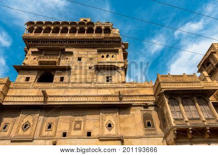 Upward picture of the front of Saalam Singh Ki Haweli carved yellow sandstone architecture in Jaisalmer known as Golden City in India.