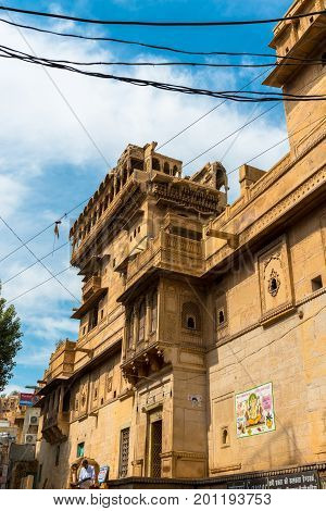JAISALMER RAJASTHAN INDIA - MARCH 07 2016: Vertical picture of the front of Saalam Singh Ki Haweli carved yellow sandstone architecture in Jaisalmer known as Golden City in India.