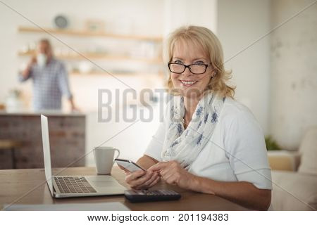 Portrait of senior woman using mobile phone at home