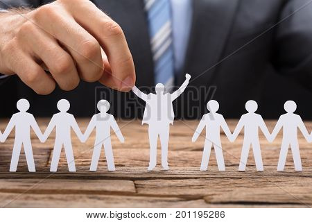 Midsection of businessman holding successful paper executive amidst team on table