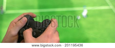 Hand holding game controller playing football game. Man Holding game controller joystick while playing console game.