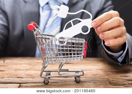 Midsection of businessman holding electric paper car over shopping cart on wooden table