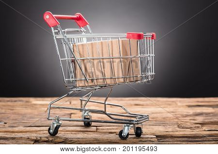 Closeup of package in shopping cart on wooden table against black background