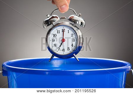 Cropped hand of businessman throwing alarm clock in blue bucket against gray background