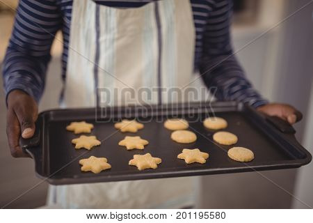 Mid section of man holding tray of cookies in kitchen at home