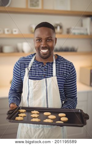 Portrait of smiling man holding tray of cookies in kitchen at home