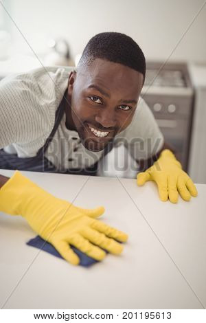 Portrait of smiling man cleaning the kitchen worktop at home