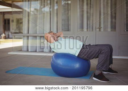 Senior man doing stretching exercise on exercise ball at veranda