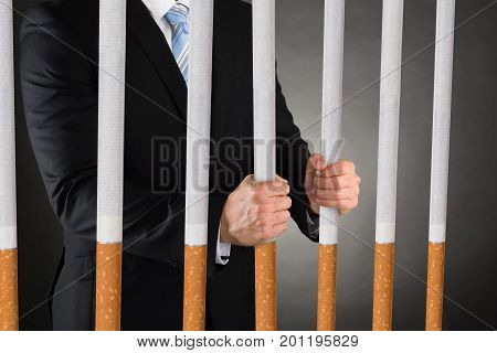 Midsection of businessman holding big cigarettes while wearing handcuffs against black background