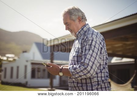 Senior man checking his mobile phone outside his house on a sunny day