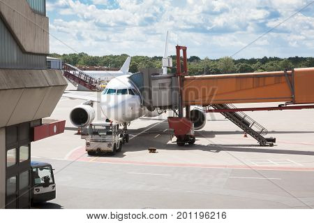 Passenger boarding bridge attached to airplane on runway