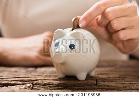 Close-up Of A Person's Hand Inserting Coin In Piggybank On Wooden Desk
