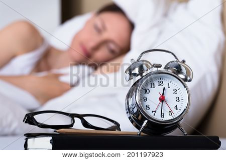 Close-up Of Eyeglasses And Alarm Clock On Table In Front Of Sleeping Woman