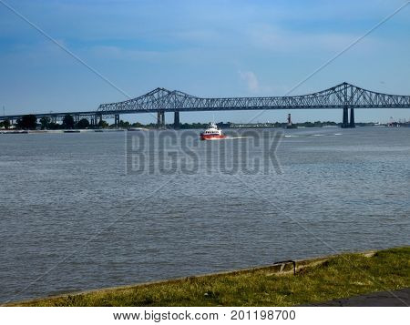 NEW ORLEANS, LOUISIANA, USA--A Coast Guard vessel sails under the Crescent City connecting bridge at the Mississippi River in New Orleans late in the afternoon in December 2016.