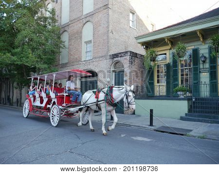 NEW ORLEANS, LOUISIANA, USA--Tourists ride a horse-drawn carriage in a tour along the streets of the French Quarter in New Orleans, Louisiana in December 2016.