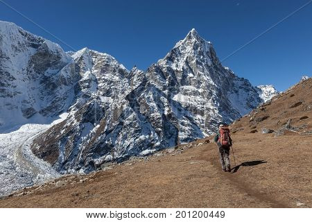 Active Woman Hiker Trekking In Nepal Towards A Hight Mountain Peak In Himalaya Landscape. Hiking Wom